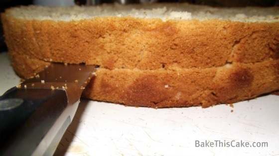 Hand slicing Lady Baltimore Cake in half for frosting by BakeThisCake