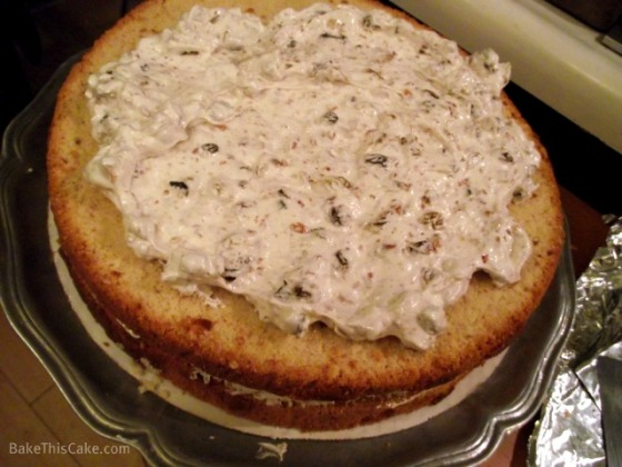 Spreading bottom 2 layers of Lady Baltimore Cake with filling by BakeThisCake