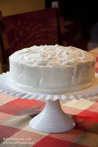 Whipped Cream Cake on milk glass plate by wooden chair BakeThisCake recipe Photo by LifeForcePhotoscom