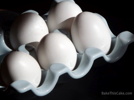 5 fresh eggs in blue ceramic egg holder Bake This Cake
