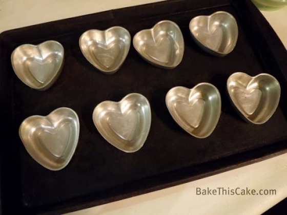 Heart pans on the cookie sheet for Cupid Cakes by Bake This Cake