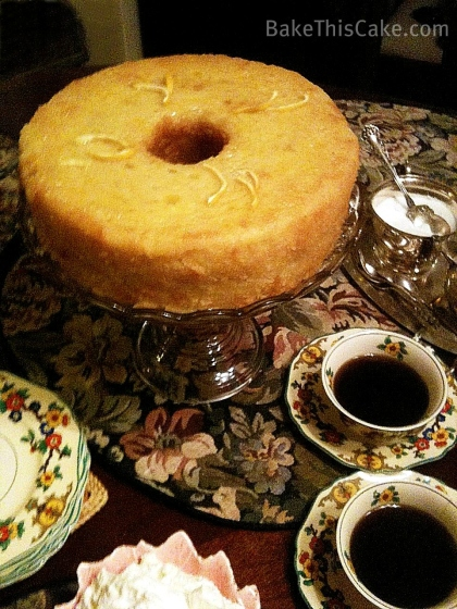 Life Force Lemon Drizzle Cake on cake platter with coffee Bake This Cake