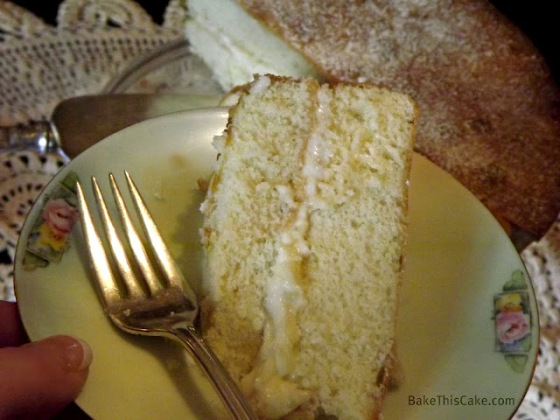 Buttermilk Cake slice on Bavarian Plate with Cake in Background BakeThisCake