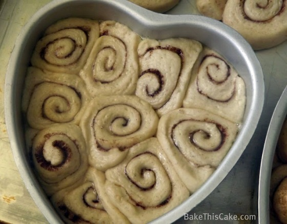 Butter cinnamon rolls rising in the pan Bake This Cake