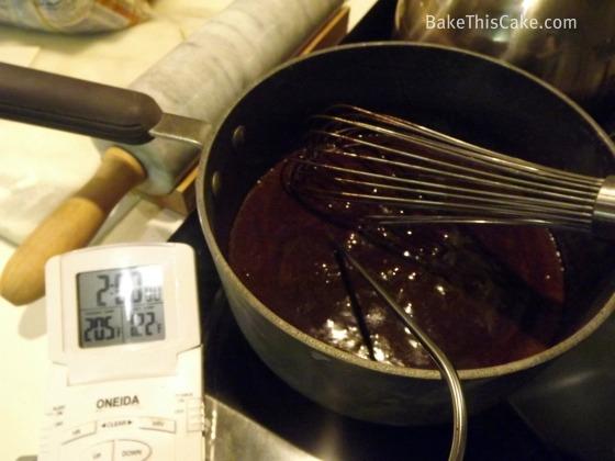Checking temp of fudge frosting BakeThisCake