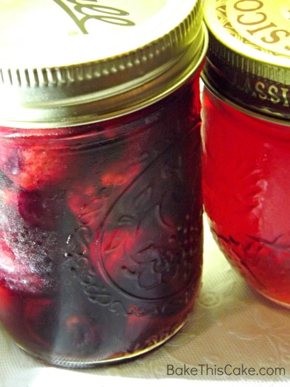 Jar of homemade cherries and jar of homemade cherry syrup Bake This Cake