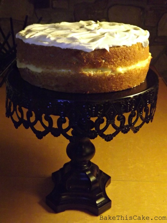 Orange Lemon Cake filled & frosted on top on black cake stand Bake This Cake