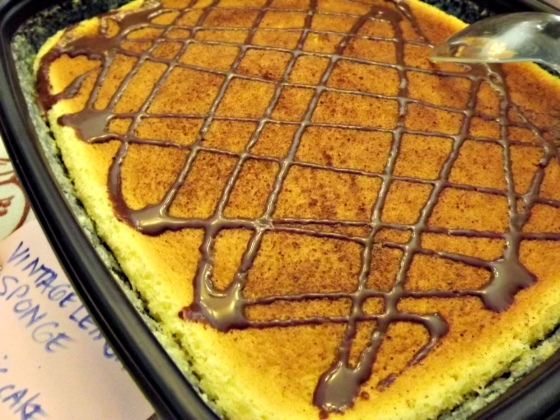 vintage lemon pudding cake with chocolate sauce and cocoa sprinkles by bake this cake