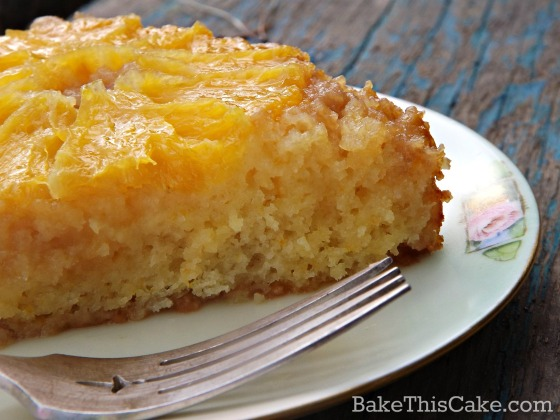 Slice of vintage orange upside down cake with honey orange soak on worn wood by bake this cake