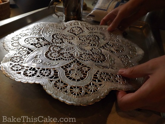Preparing the doiley for the powdered sugar cake pattern by bake this cake