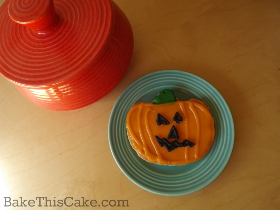 Pumpkin Sugar Cookie on a blue Bauer plate and orange candy bowl by bake this cake
