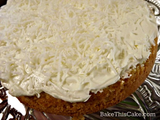 Filling Grandma's Golden Coconut Cake with heirloom custard frosting by bake this cake